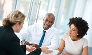 Shot of a young man and woman meeting with a financial planner in a modern office